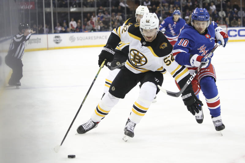 Boston Bruins center Sean Kuraly (52) controls the puck skating ahead of New York Rangers left wing Artemi Panarin (10) during the first period of an NHL hockey game, Sunday, Feb. 16, 2020, at Madison Square Garden in New York. (AP Photo/Mary Altaffer