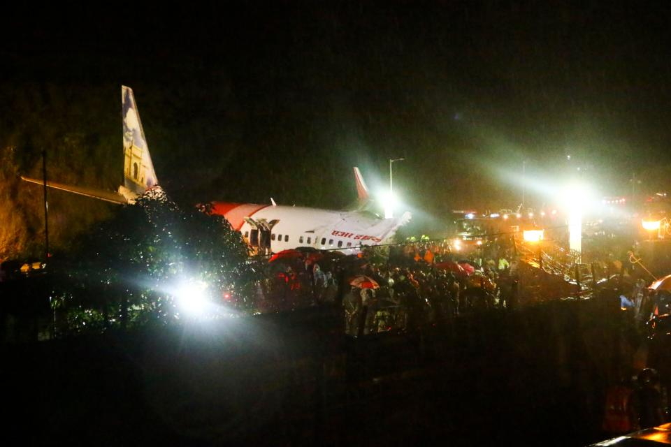 First responders gather around the wreckage of an Air India Express jet, which was carrying more than 190 passengers and crew from Dubai, after it crashed by overshooting the runway at Calicut International Airport in Karipur, Kerala, on August 7, 2020. - At least 14 people died and 15 others were critically injured when a passenger jet skidded off the runway after landing in heavy rain in India, police said on August 7. (Photo by Favas JALLA / AFP) (Photo by FAVAS JALLA/AFP via Getty Images)