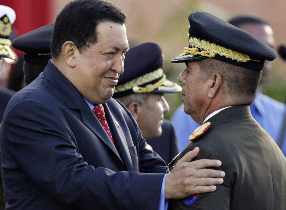 FILE - In this July 3, 2012 file photo, Venezuela's President Hugo Chavez, left, greets Major General Wilmer Barrientos after he was promoted at a military ceremony in Fuerte Tiuna military base in Caracas, Venezuela. A former paratrooper, Chavez enjoys explicit support from two of the country's top military leaders, Defense Minister Adm. Diego Molero and chief strategic operational officer, top army Gen. Wilmer Barrientos. (AP Photo/Ariana Cubillos, File)