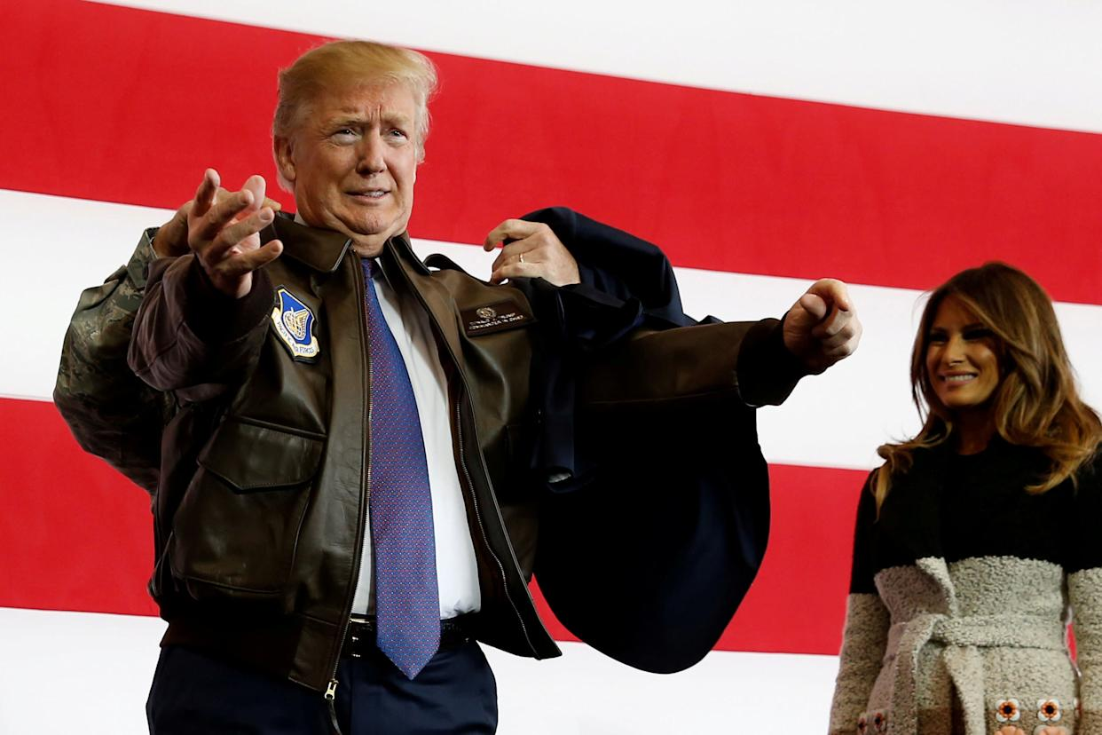 President Donald Trump puts on a U.S. Pacific Air Forces bomber jacket before delivering remarks to members of the U.S. military at Yokota Air Base, Japan.