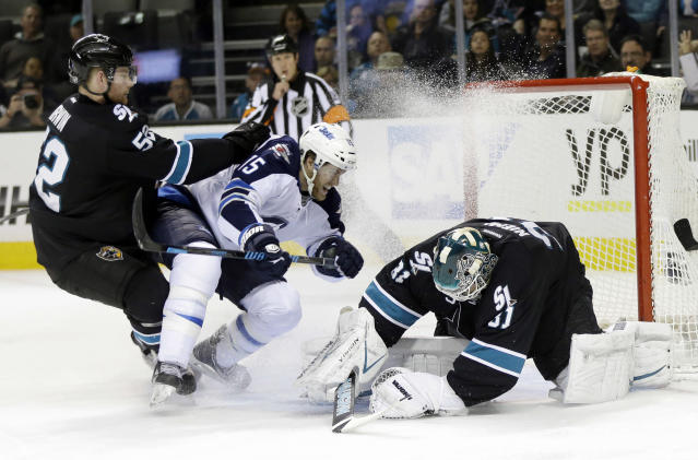 San Jose Sharks goalie Antti Niemi, right, of Finland, stop a shot next to Winnipeg Jets' Matt Halischuk (15) and teammate Matt Irwin (52) during the second period of an NHL hockey game on Thursday, March 27, 2014, in San Jose, Calif. (AP Photo/Marcio Jose Sanchez)