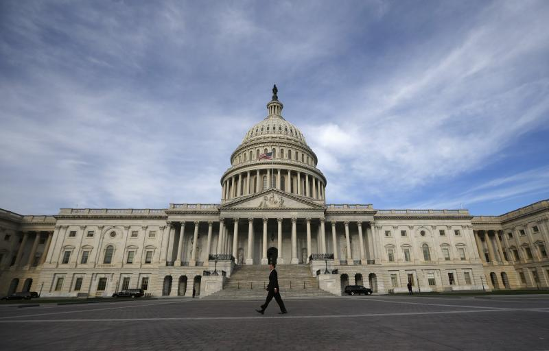 A lone worker passes by the U.S. Capitol building in Washington, October 8, 2013. A few faint glimmers of hope surfaced in the U.S. fiscal standoff, both in Congress and at the White House, with President Barack Obama saying he would accept a short-term increase in the nation's borrowing authority to avoid a default. REUTERS/Jason Reed (UNITED STATES - Tags: POLITICS TPX IMAGES OF THE DAY)