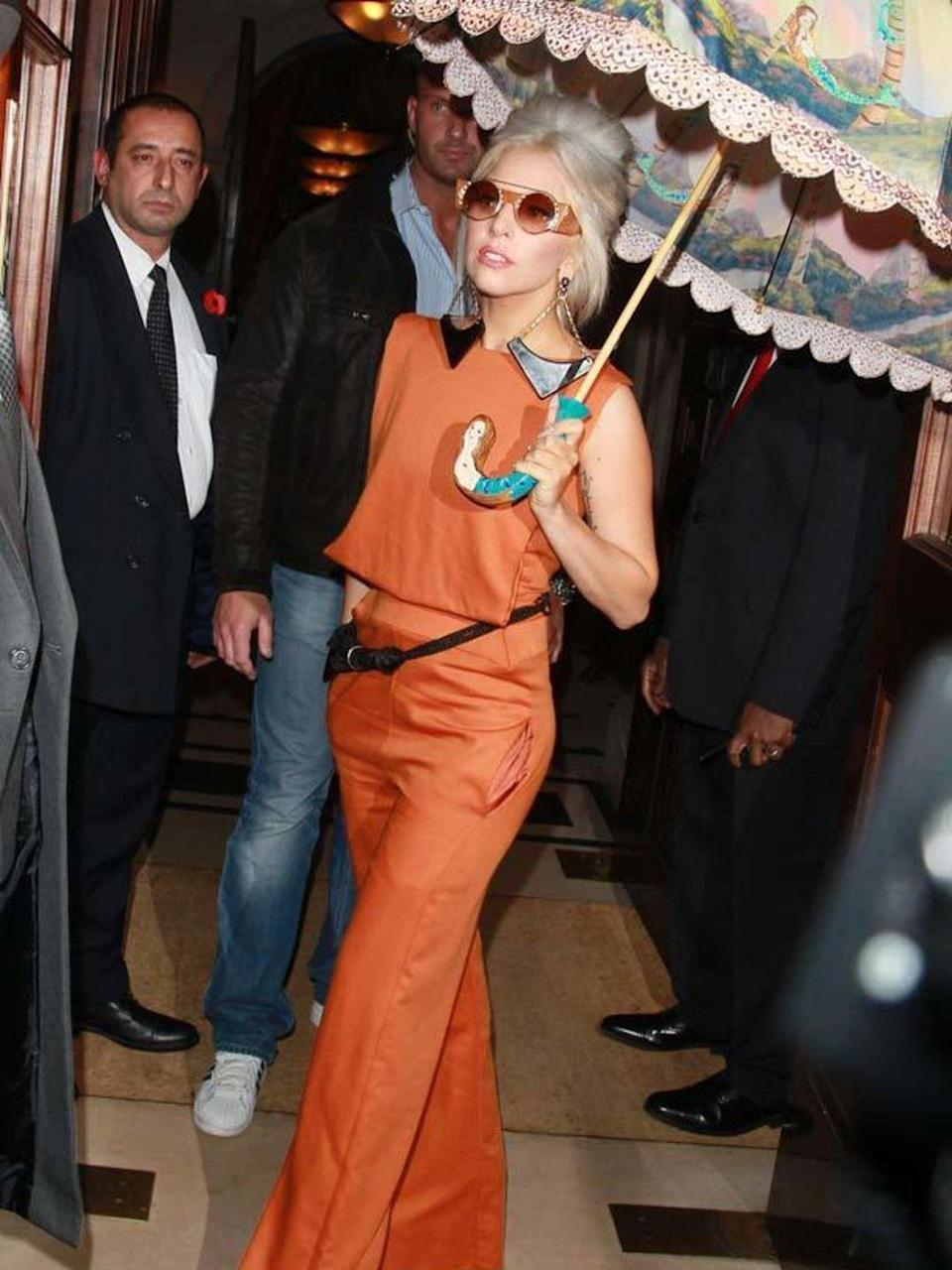 <p>Lady Gaga goes for bold in this tangerine top with wide leg trousers complete with round sunglasses and printed umbrella in London, November 2012.</p>