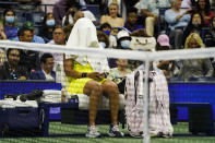 Naomi Osaka, of Japan, covers her head between sets against Leylah Fernandez, of Canada, during the third round of the US Open tennis championships, Friday, Sept. 3, 2021, in New York. (AP Photo/John Minchillo)