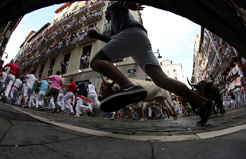 Revellers sprint in front of bulls and steers during the second running of the bulls at the San Fermin festival in Pamplona, Spain, July 8, 2019. (Photo: Jon Nazca/Reuters)