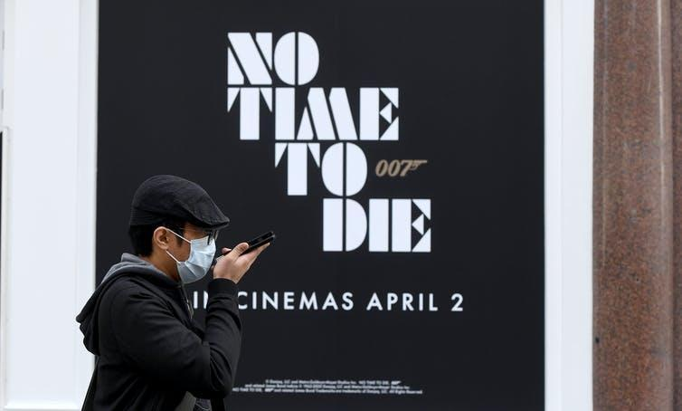 Face-masked person walks past poster for James Bond with the words No Time To Die and