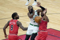 Boston Celtics' Jaylen Brown (7) loses control of the ball off the defense of Chicago Bulls' Thaddeus Young as Patrick Williams watches during the first half of an NBA basketball game Monday, Jan. 25, 2021, in Chicago. (AP Photo/Charles Rex Arbogast)