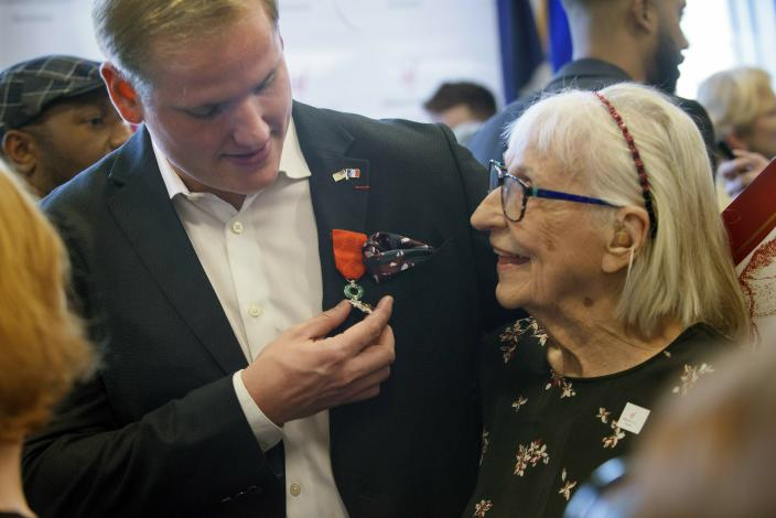 Spencer Stone, left, shows off his French Legion of Honor medal to his grandmother Dorothy Eskel following a French Naturalization Ceremony for Stone and his two friends Anthony Sadler and Alek Skarlatos in Sacramento, Calif., Thursday, Jan. 31, 2019. The three men were heralded as heroes when they subdued an armed terrorist on a train in France in 2015. Today they were granted French citizenship. (AP Photo/Randall Benton)
