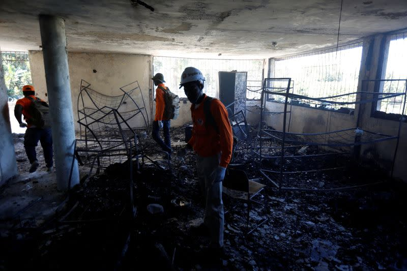 Civil protection workers stand inside a bedroom at an orphanage after it was destroyed in a fire, in Port-au-Prince
