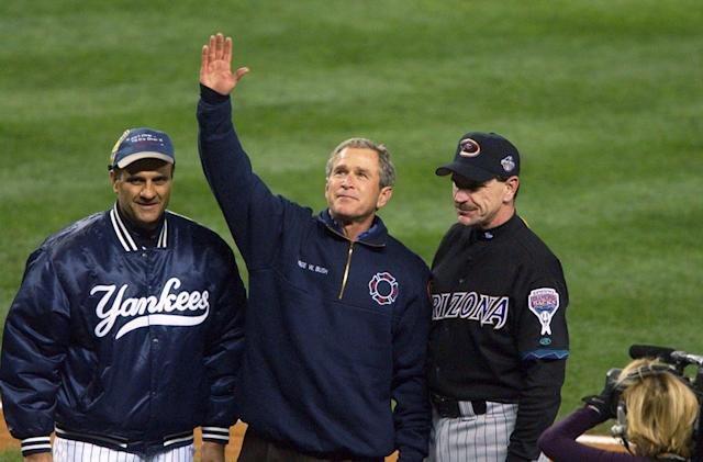 President George W. Bush, standing with New York Yankees' manager Joe Torre (left) and Arizona Diamondbacks manager Bob Brenly acknowledges applause from crowd at Yankee Stadium before start of Game 3 of the World Series on Oct. 30, 2001. (Howard Earl Simmons/NY Daily News Archive via Getty Images)