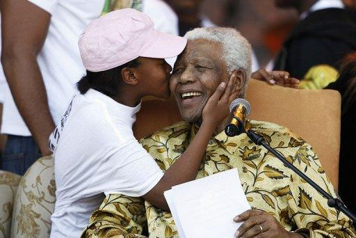 <p>Nelson Mandela receives a kiss from one of his grandchildren in Pretoria in 2008. The former South African leader turned 94 on Wednesday, with the nation's 12 million schoolchildren starting their day by singing a special birthday song as Mandela asked the world to honour his legacy by performing community service.</p>