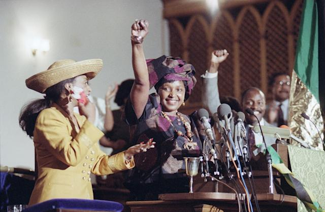 <p>Winnie Mandela, right, raises her fist to cheer the crowd as Jacqueline Jackson, wife of Jesse Jackson, left, applauds her during a church service on June 24, 1990, in Washington. The service honored South African women. (Photo: Jeff Markowitz/AP) </p>