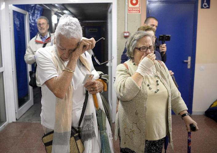Two women cry as they arrive at a polling station to cast their ballot in Barcelona (AFP Photo/Josep LAGO)