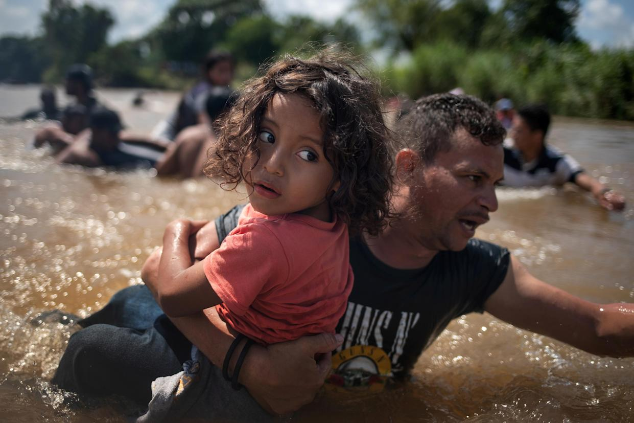 A man, part of a caravan of migrants from Central America en route to the U.S., carries a girl through the Suchiate River into Mexico from Guatemala, Oct. 29, 2018. (Photo: Adrees Latif/Reuters)