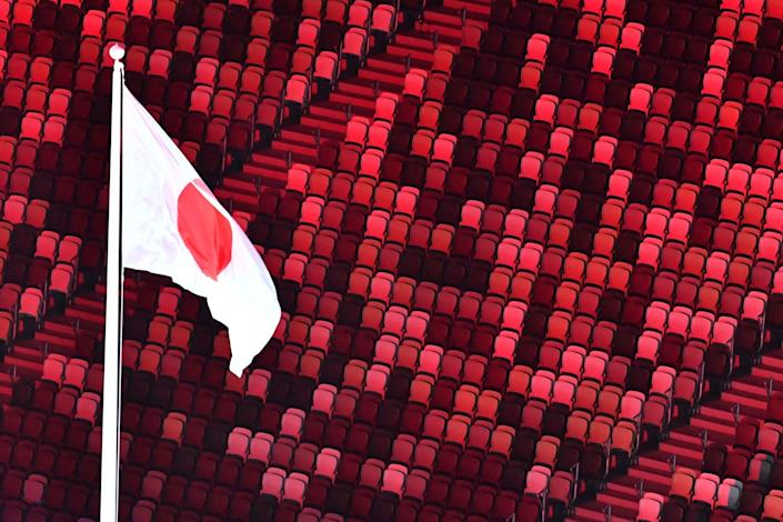 The Japanese flag wave above empty seats during the Opening Ceremony.