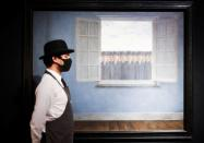 A gallery assistant poses alongside artwork titled 'Le Mois des Vendanges' by painter Rene Magritte during a photocall at Christie's auction house, in London