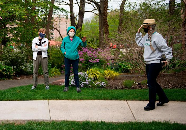 Residents of the Goodwin House senior living community greet each other, wearing masks for protection, in a garden in Arlington, Va. on April 14, 2020.