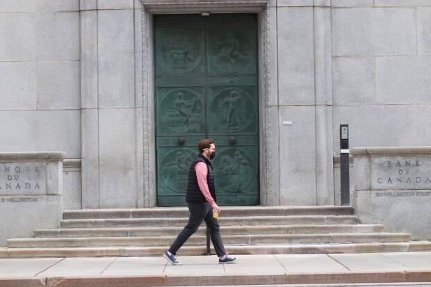 A man wearing a COVID-19 mask walks past the Bank of Canada building on Wellington Street in Ottawa on April 17, 2021. (Trevor Pritchard/CBC - image credit)