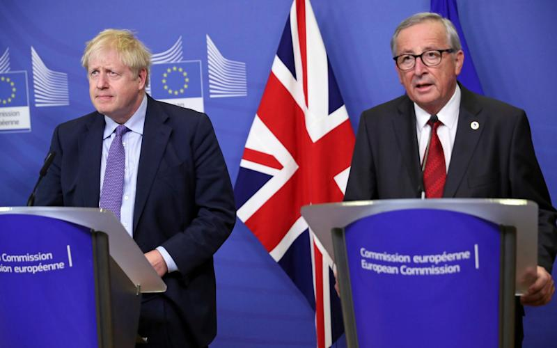 Boris Johnson (left) speaks alongside European Commission President Jean-Claude Juncker - AP