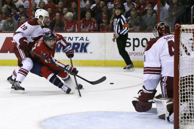 Washington Capitals right wing Tom Wilson (43) tries to shoot the puck as he struggles with Phoenix Coyotes defenseman Chris Summers (20), while Coyotes goalie Mike Smith (41) moves to defend during the first period of an NHL hockey game, Saturday, March 8, 2014, in Washington. (AP Photo/Carolyn Kaster)