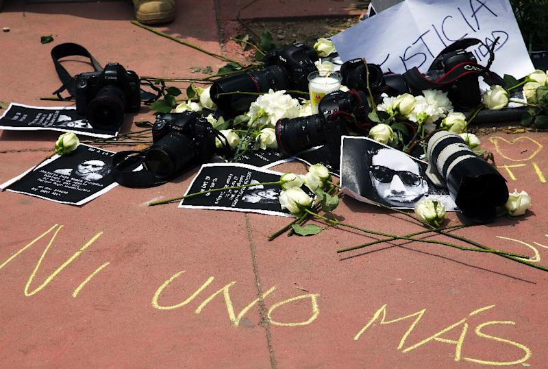 Signs, cameras and flowers are seen during a demonstration to demand justice in the murder of Mexican photojournalist Ruben Espinosa in Guadalajara City, on August 2, 2015 (AFP Photo/Hector Guerrero)