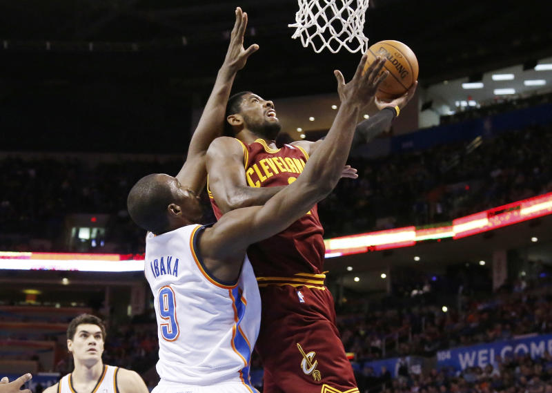 Cleveland Cavaliers guard Kyrie Irving (2) shoots in front of Oklahoma City Thunder forward Serge Ibaka (9) during the second quarter of an NBA basketball game in Oklahoma City, Wednesday, Feb. 26, 2014. (AP Photo/Sue Ogrocki)