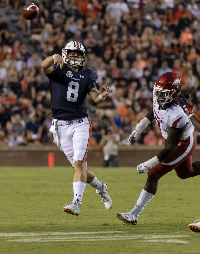 Auburn quarterback Jarrett Stidham (8) throws on the run with Arkansas defensive lineman Briston Guidry (7) in pursuit during the first half of an NCAA college football game, Saturday, Sept. 22, 2018, in Auburn, Ala. (AP Photo/Vasha Hunt)