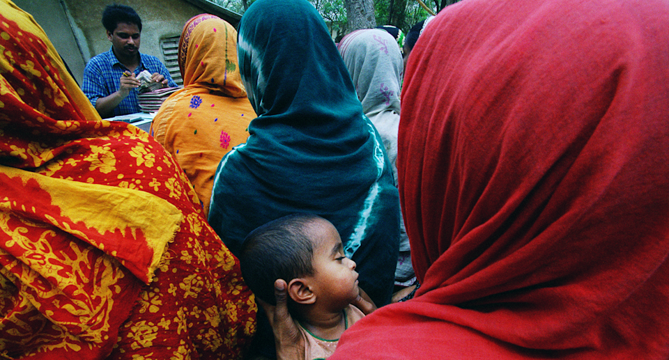 A historical photo of women in colourful headscarves lining up for microcredit loans. One carries a baby.