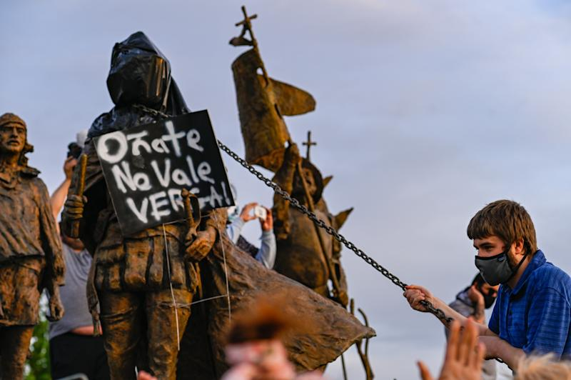 Protesters use a chain to try to remove the Juan de Oñate statue in Albuquerque. (Anthony Jackson/Albuquerque Journal via Zuma Wire)