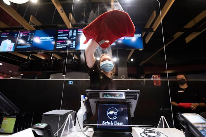 Sara Commarota cleans the plexiglass shield at the AMC Highlands Ranch 24 on August 20, 2020 in Highlands Ranch, Colorado. (Photo by Tom Cooper/Getty Images)