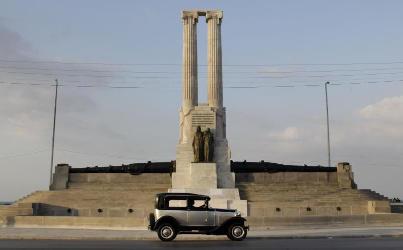In this Tuesday, Feb. 12, 2013 photo, a person drives a classic car past the restored USS Maine monument in Havana, Cuba. The monument was erected in 1925 in honor of U.S. sailors who died in 1898 when the USS Maine ship sank off the Havana Harbor. The years since have been unkind to the twin-columned monument, and to U.S.-Cuba ties. But while relations between Washington and Havana remain in deep freeze, the monument, at least, is now getting a facelift. (AP Photo/Franklin Reyes)