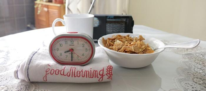 "Grey and red coloured alarm clock showing 8.30, on top of a ""Good Morning"" towel, beside a white bowl of cereal, a white mug of coffee and a black radio."