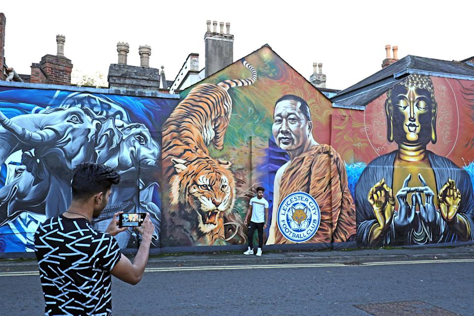 A man takes a picture of his friend standing next to a mural of the Leicester owner Vichai Srivaddhanaprabha (Aaron Chown/PA Wire)