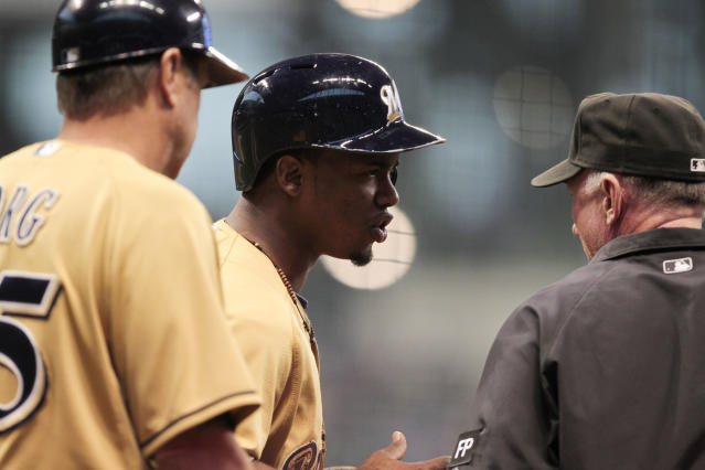 Milwaukee Brewers' Jean Segura, center, argues with an umpire , right, after being tagged out at first base during the fourth inning of a baseball game against the Cincinnati Reds, Sunday, Sept. 15, 2013, in Milwaukee. (AP Photo/Andy Manis)