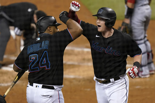 Miami Marlins' Garrett Cooper, right, celebrates with Jesus Aguilar (24) after hitting a two-run home run during the third inning of the team's baseball game against the Washington Nationals, Saturday, Sept. 19, 2020, in Miami. (AP Photo/Lynne Sladky)