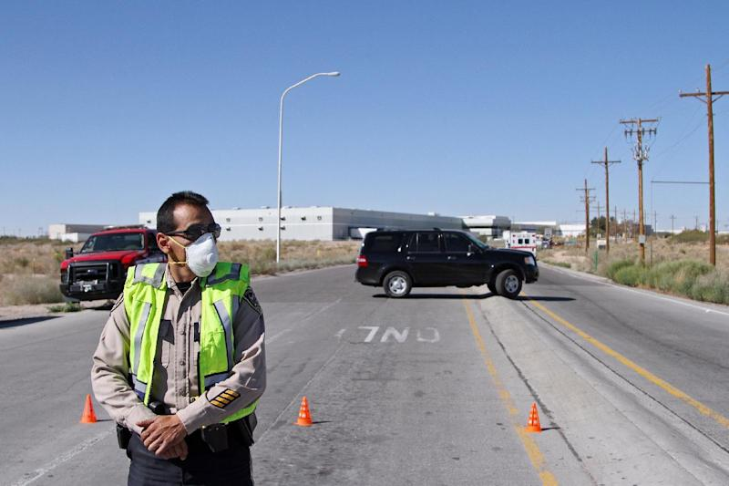 A police officer blocks an intersection outside the Santa Teresa Industrial Park in Santa Teresa, N.M. on Tuesday, Oct. 30, 2012. The industrial park near the border crossing at Santa Teresa was evacuated and the nearby airport was closed because of an unknown hazardous material release that sickened about 200 people. (AP Photo/Juan Carlos Llorca)
