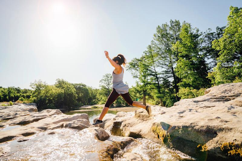 Caucasian woman jumping on rocks near river (Photo: Getty Images)