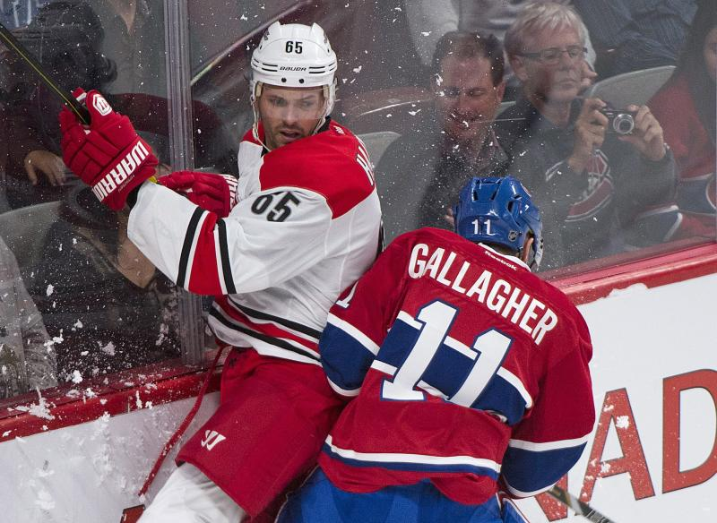 Montreal Canadiens' Brendan Gallagher, right, checks Carolina Hurricanes' Ron Hainsey into the boards during the first period of a preseason NHL hockey game Saturday, Sept. 21, 2013, in Montreal. (AP Photo/The Canadian Press, Graham Hughes)