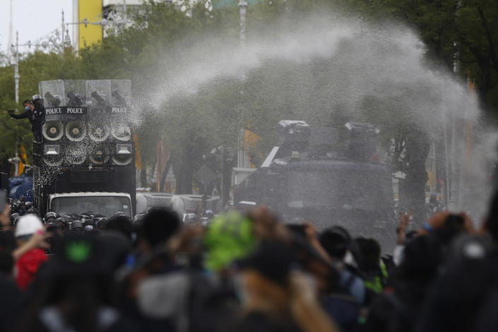 Police use water cannon to disperse protesters as they march to Government House in Bangkok, Thailand Sunday, July 18, 2021. Hundreds of anti-government protesters rallied on Sunday despite the government's recent measures to prohibit the gathering of more than 5 people in the capital to curb the COVID-19 pandemic. Protesters demanded the resignation of Prime Minister Prayuth Chan-ocha and his cabinet. (AP Photo/Anuthep Cheysakron)
