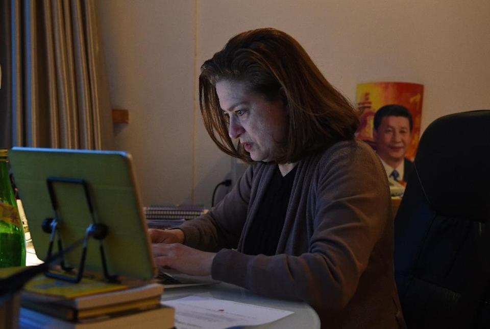 Ursula Gauthier, the correspondent for French news magazine L'Obs, works at her desk in her apartment in Beijing on December 26, 2015 (AFP Photo/Greg Baker)
