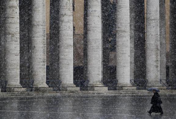 A priest walks as it snows in Saint Peter's Square at the Vatican February 12, 2010.