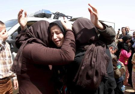 Members of the minority Yazidi sect who were newly released hug each other on the outskirts of Kirkuk April 8, 2015. REUTERS/Ako Rasheed