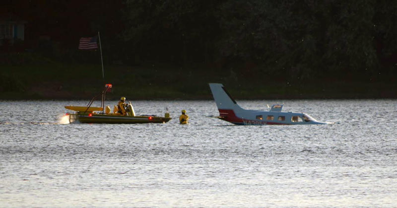 Emergency personnel secure a small plane that landed in in a shallow section of the Susquehanna River a few miles from the Three Mile Island nuclear power station, Friday, Oct. 4, 2019 near Middletown, Pa. Susquehanna Regional Airport Authority executive director Tim Edwards said the pilot and the single-engine plane's lone passenger were taken to a hospital for treatment. The Federal Aviation Administration says the two on board exited the Piper PA-46 onto a wing. (Garrett Doane/The Sun via AP)