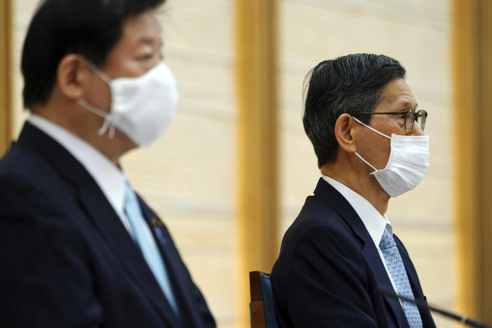 President of the Japan Community Healthcare Organization Shigeru Omi, right, attends a government task force meeting on the COVID-19 measures at the prime minister's office Friday, April 9, 2021, in Tokyo. Japan announced Friday that it will raise the coronavirus alert level in Tokyo to allow tougher measures to curb the rapid spread of a more contagious variant ahead of the Summer Olympics. (AP Photo/Eugene Hoshiko, Pool)