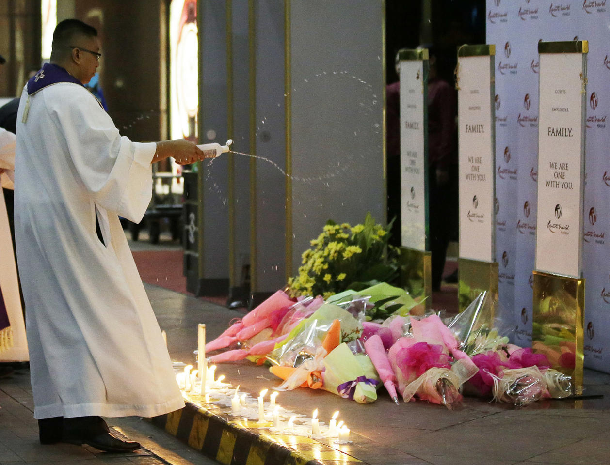 <p>A Catholic priest sprinkles holy water on a memorial during a mass for victims of an attack at the Resorts World Manila complex, Friday, June 2, 2017, in Manila, Philippines. (Photo: Aaron Favila/AP) </p>