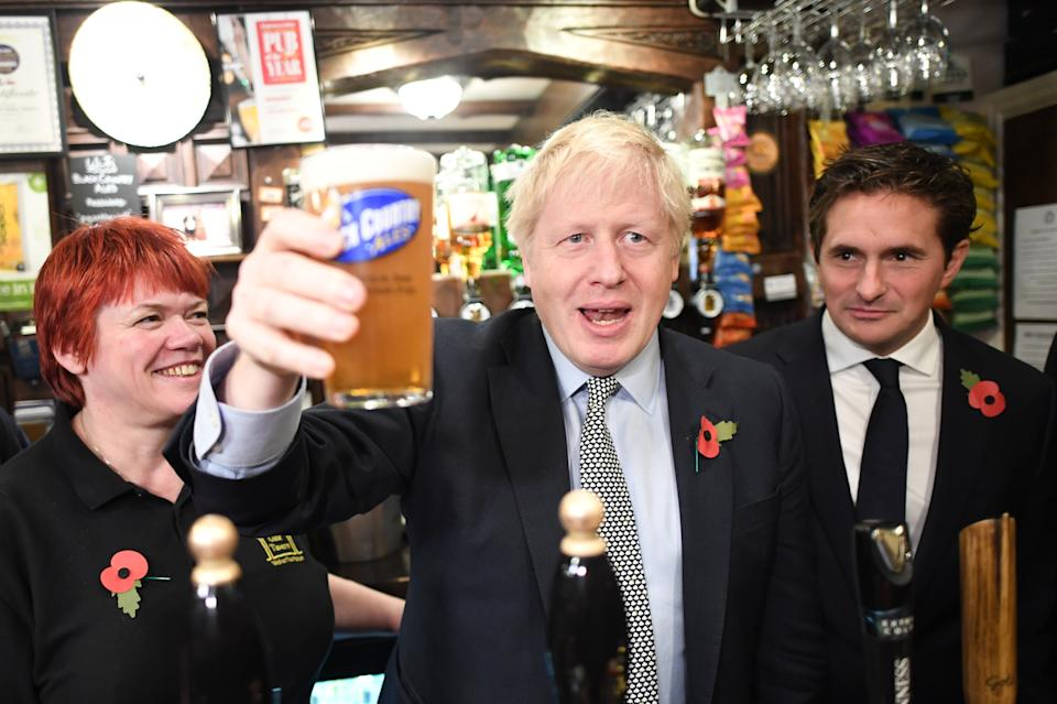 Prime Minister Boris Johnson, raises a pint watched by Defence Minister Johnny Mercer (right) as he meets with military veterans at the Lych Gate Tavern in Wolverhampton. (Photo by Stefan Rousseau/PA Images via Getty Images)