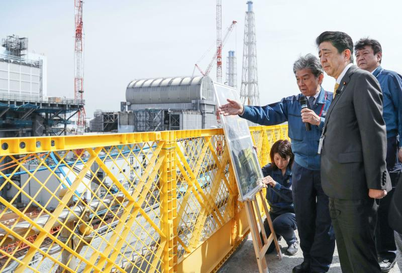 Japanese Prime Minister Shinzo Abe, foreground, visits Fukushima Dai-ichi nuclear power plant in Okuma, Fukushima prefecture, Japan, Sunday, April 14, 2019, to inspect the reconstruction effort following the tsunami, quake and nuclear accident in 2011. (Kyodo News via AP)