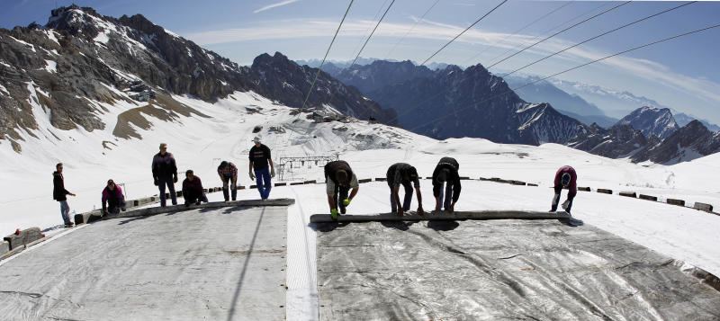 FILE - In this May 10, 2011 file photo, workers cover the glacier with oversized plastic sheets on the peak of Germany's highest mountain Zugspitze (2962 meters) near Garmisch-Partenkirchen, southern Germany. The sheets are meant to keep the glacier from melting during the summer months. It's Plan B in the fight against climate change: cooling the planet by sucking heat-trapping CO2 from the air or reflecting sunlight back into space. The U.N.'s expert panel on climate change is under pressure from both sides this week in Berlin, Germany, as it considers whether geoengineering should be part of the toolkit that governments use to keep global warming in check. (AP Photo/Matthias Schrader, File)