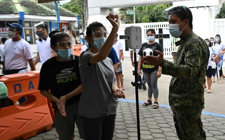 Coronavirus precautions are in place as people in the Philippine capital flock to graveyards ahead of All Saints' Day