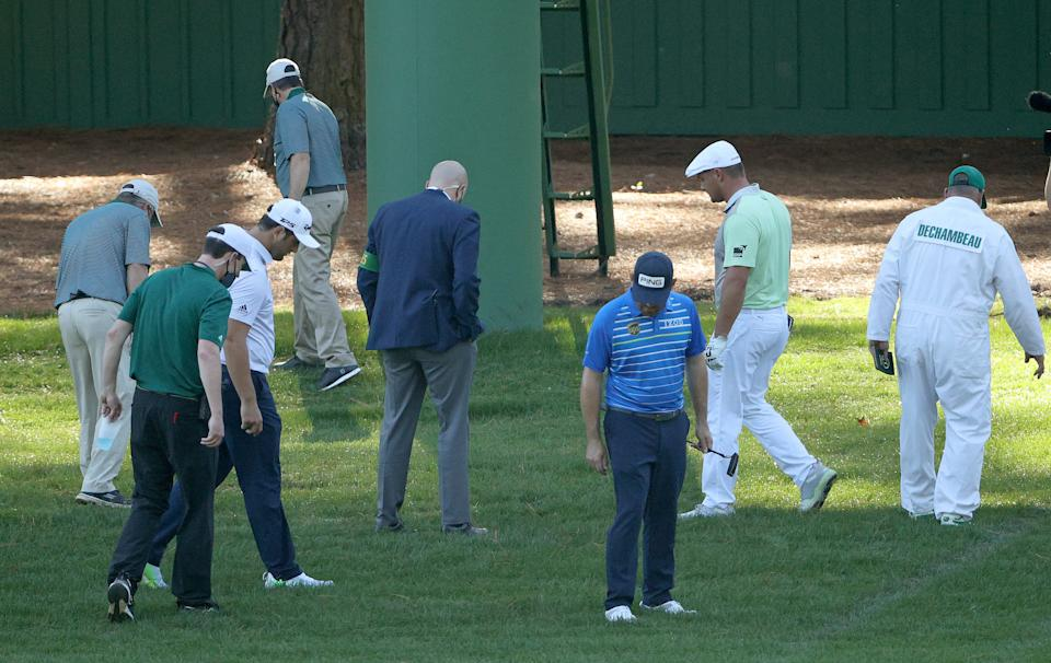 Bryson DeChambeau looks for his ball with Jon Rahm and Louis Oosthuizen on the third hole during the second round of the Masters at Augusta National Golf Club.